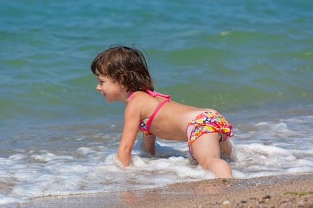 child swimsuit: Beach vacation. Happy child in the sea
