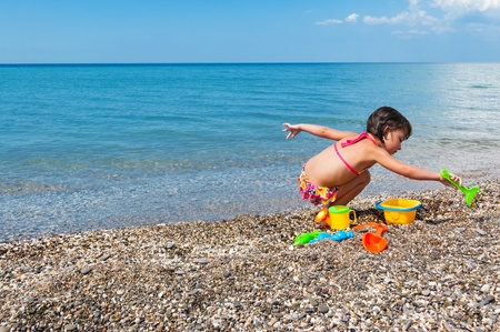 playing in the sea: Little girl playing with toys on the beach Stock Photo