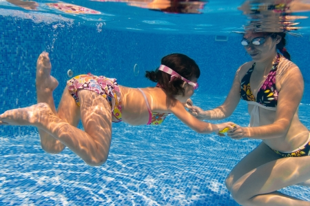 swimming goggles: Underwater family in swimming pool. Mother teaching her child Stock Photo