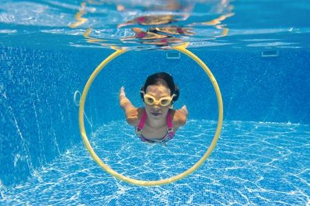 girl underwater: Happy lachende jongen onder water in zwembad