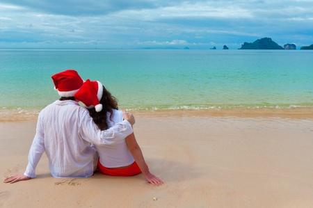 Vánoční tropickou dovolenou. Romantický pár v santa klobouky na pláži Reklamní fotografie