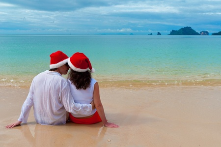 Christmas tropical vacation. Romantic couple in santa hats on beach photo