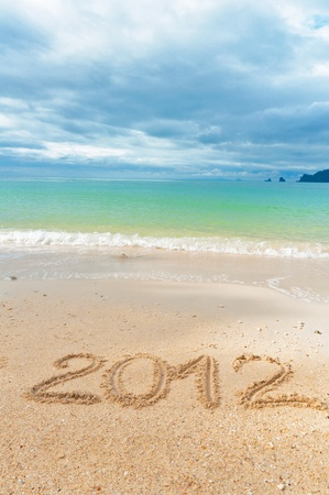 Numbers 2012 on tropical beach sand - holiday background photo