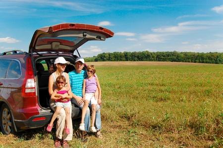 Family of four near their car on vacation Stock Photo