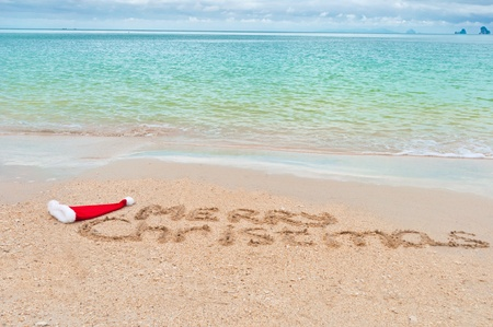 Holiday background - Merry Christmas written on tropical beach sand Stock Photo