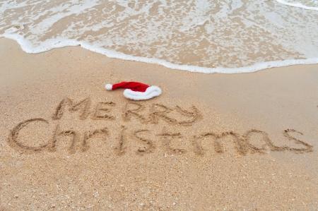 Ubytování v pozadí - Merry Christmas napsaný na tropické pláži písku