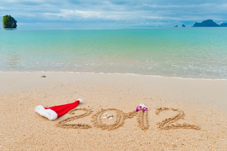 Numbers 2012 and santa hat on tropical beach sand - holiday background