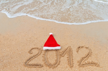 Numbers 2012 and santa hat on tropical beach sand - holiday background Stock Photo - 10492741