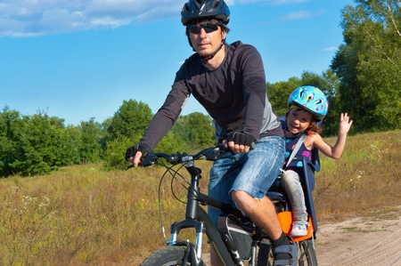 Family cycling. Father with happy kid riding bicycle outdoors photo