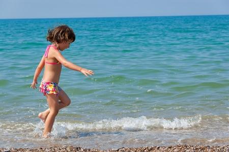Child and sea. Running kid on the beach photo