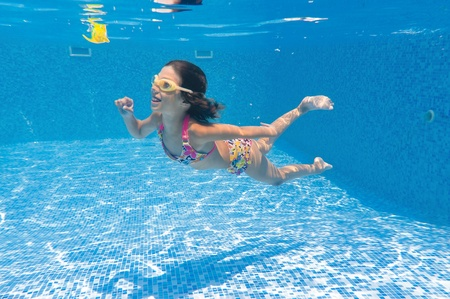 Happy smiling underwater kid playing in swimming pool photo