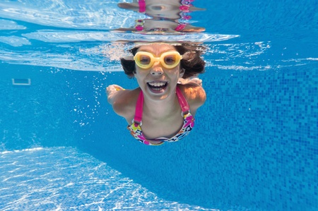 Happy smiling underwater kid in swimming pool photo