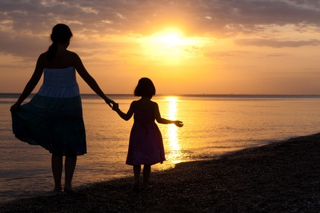 mother daughter: Mother and kid on sunset beach