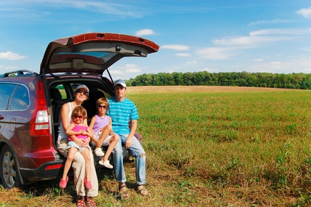 Family of four near their car on vacation Stock Photo - 10531933