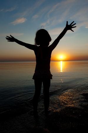 Child on sunset beach photo