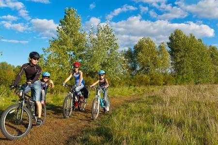 Extérieur en famille à vélo. Heureux parents de deux enfants sur les vélos