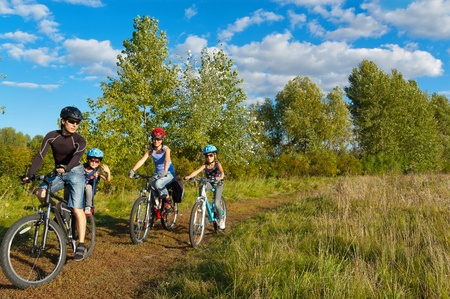 helmet seat: Family cycling outdoors. Happy parents with two kids on bikes