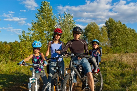 Family cycling outdoors. Happy parents with two kids on bikes photo