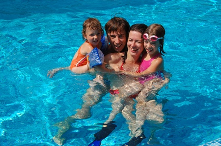splash pool: Family vacation. Parents with children in swimming pool Stock Photo