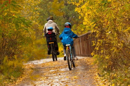 fall fun: Family cycling outdoors, golden autumn in park Stock Photo