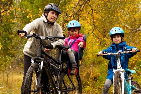 Family cycling outdoors, golden autumn in park photo