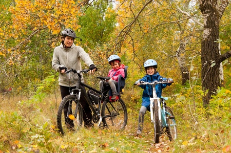 happy family nature: Family cycling outdoors, golden autumn in park Stock Photo