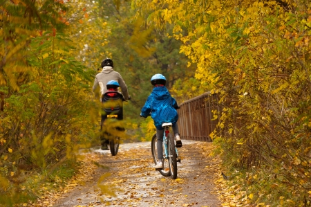 Family cycling outdoors, golden autumn in park Reklamní fotografie