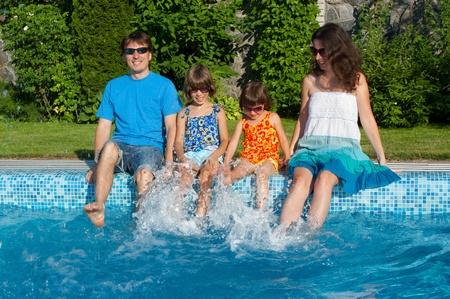 Rodinná dovolená. Rodiče se dvěma dětmi baví u bazénu Reklamní fotografie