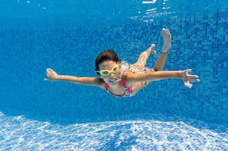Happy smiling underwater child in swimming pool, beautiful girl swim Stock Photo - 10922348