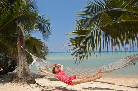 Woman relaxing on hammock on tropical beach photo