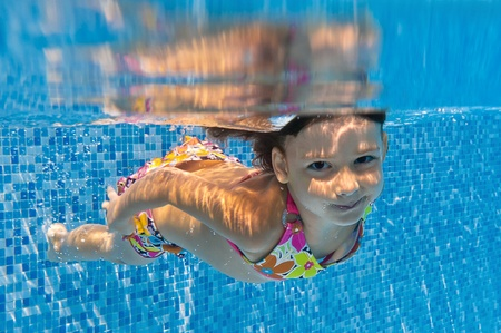 Happy smiling underwater child in swimming pool. Kids sport photo
