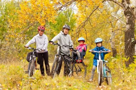 Gelukkig gezin fietsen buiten, lachende ouders met kinderen op de fiets, gouden herfst in het park Stockfoto