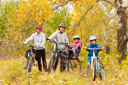 Happy family cycling outdoors, smiling parents with kids on bicycles, golden autumn in park photo