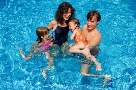 splash pool: Familia feliz con los ni�os en la piscina. Sonre�r a los padres y los ni�os en las vacaciones de verano Foto de archivo