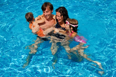 pool fun: Happy family with kids in swimming pool. Smiling parents and children on summer vacation
