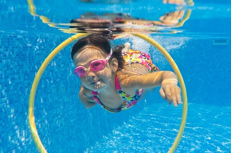 swim goggles: Happy smiling underwater child in swimming pool. Little girl swims. Kids sport Stock Photo