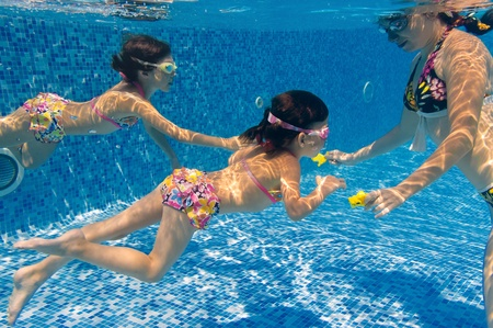 Underwater family in swimming pool. Mother teaching her kids photo