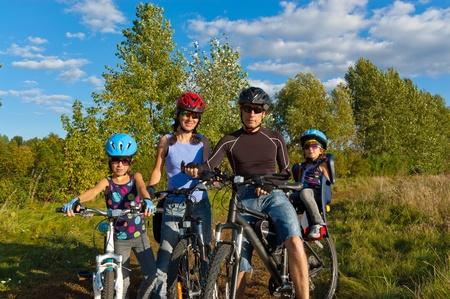Rodina na kole venku. Šťastní rodiče s dvěma dětmi na kolech