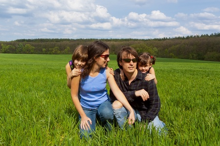 Happy family with two kids having fun outdoors on green field, spring vacation photo