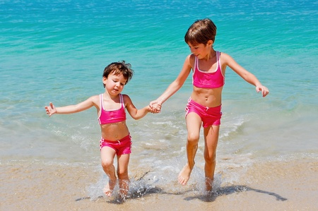 Happy kids on beach vacation. Two little girls running near sea photo