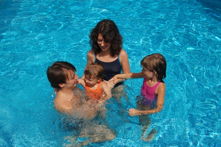 pool preteen: Happy family with kids in swimming pool. Smiling parents and children on summer vacation
