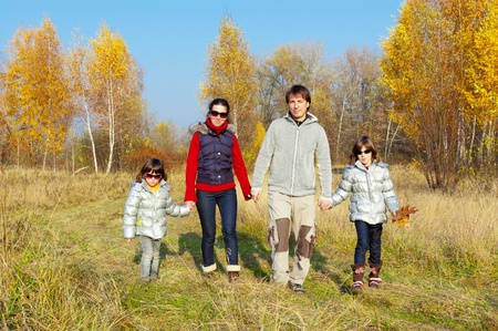 Happy smiling family walking in autumn park. Parents with kids outdoodrs photo