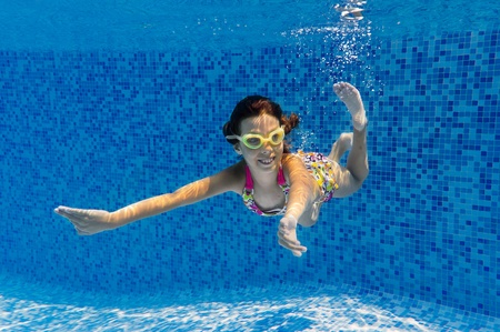 Happy smiling underwater child in swimming pool, beautiful girl swims and having fun. Child sport on summer vacation photo