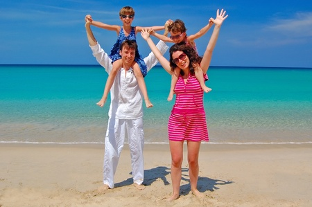 Family beach vacation. Happy smiling parents with kids having fun on beach near sea