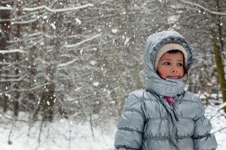 Happy child having fun in winter forest. Little girl outdoors