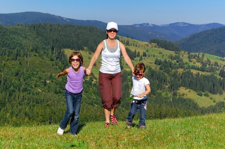 Happy active family on summer vacation in mountains. Smiling mother and kids having fun outdoors Stock Photo