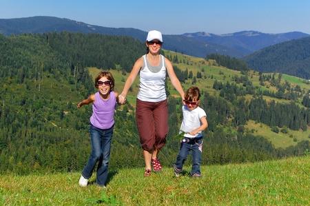 Happy aktivní rodina na letní dovolenou v horách. Usmívající se matka a děti baví venku