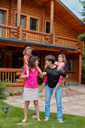 wooden house: Happy smiling family near wooden house. Parents having fun with kids in garden. Vertical image