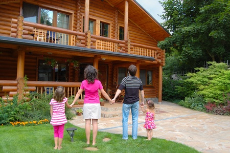 Happy family with two kids looking at the wooden house photo