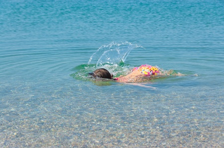 Happy child swims underwater in sea  Little girl on summer beach vacation photo